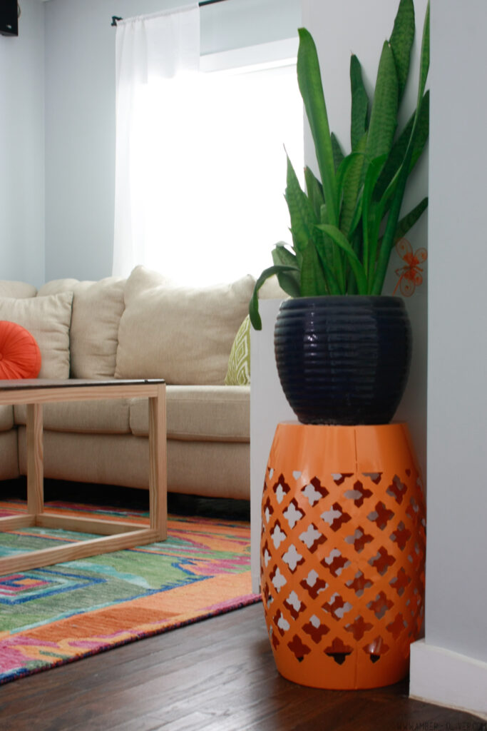 orange plant stand in  colorful living room