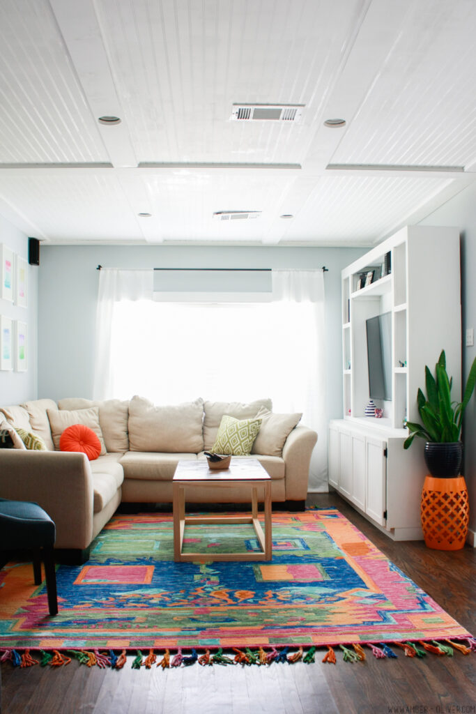 amazing colorful living room with DIY entertainment center and colorful rug