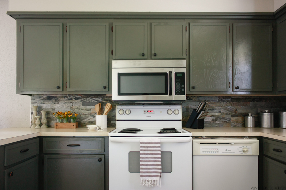 Kitchen remodel on a budget! Dark painted cabinets, peel and stick backsplash, and updated old cabinet doors!