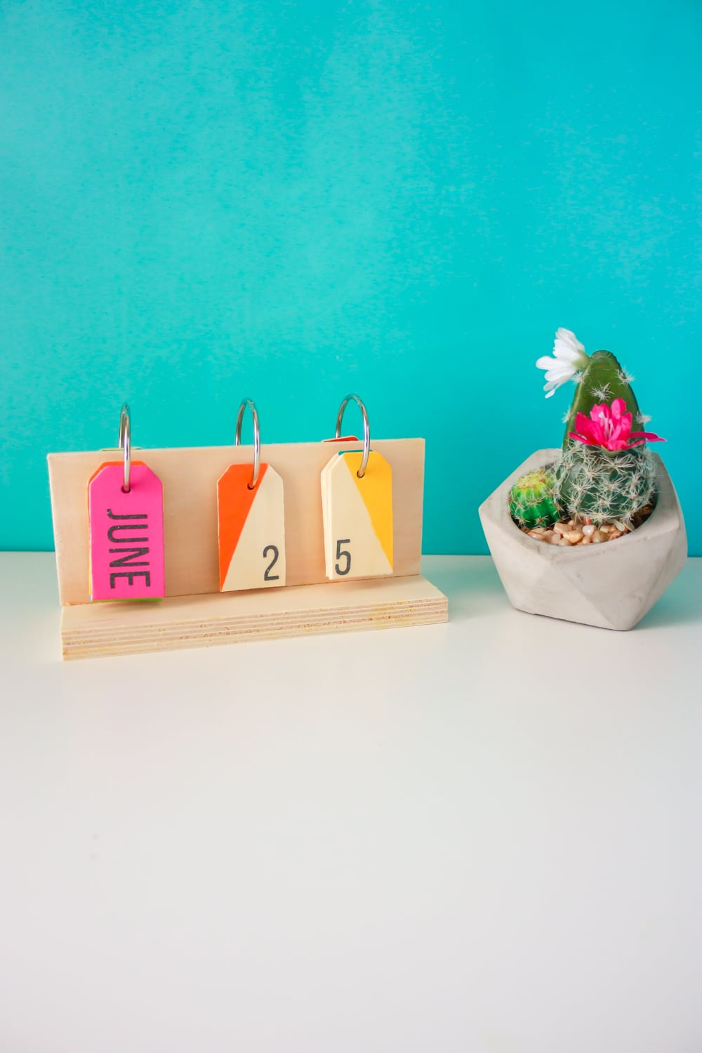 How to make a perpetual calendar for a colorful way to display the date! You'll need wood pieces, wooden tags, glue, metal rings, paint, and a drill.