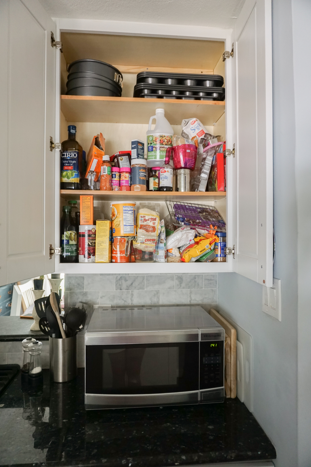 An unorganized baking cabinet - Organizing baking supplies is easy with cork tiles, command hooks, vinyl labels, and a beautiful craft paper to line the cabinet.