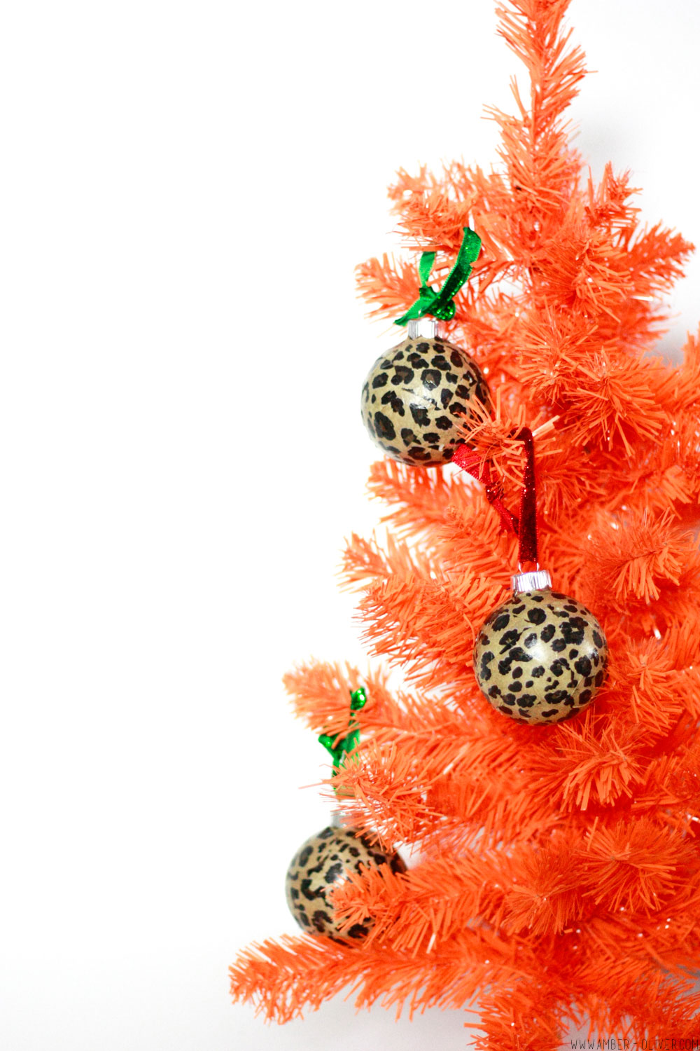 DIY Leopard Print Ornaments hung on an orange tree. these are Easy to make modge podge tissue paper Christmas ornaments!