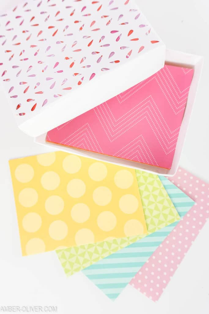 stack of colorful cards with a handmade cardstock box to hold them
