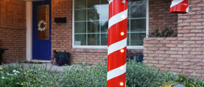 DIY Lighted PVC Candy Cane standing tall outside house