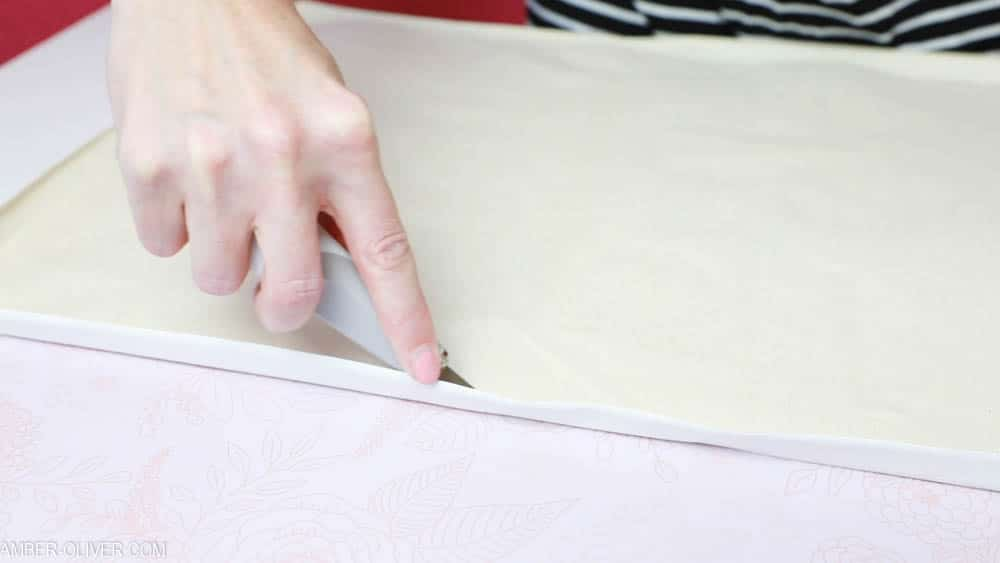 cutting excess canvas to create reverse canvas signs