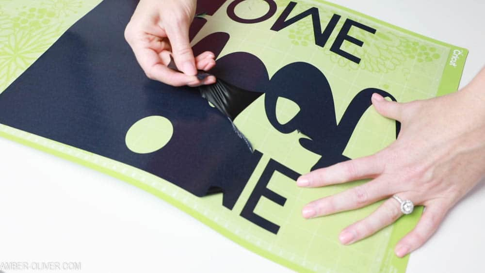 removing excess vinyl to create reverse canvas signs