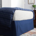 room with navy diy bedskirt and colorful rug