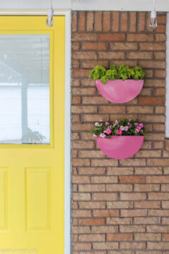 pink painted metal planters by a yellow door