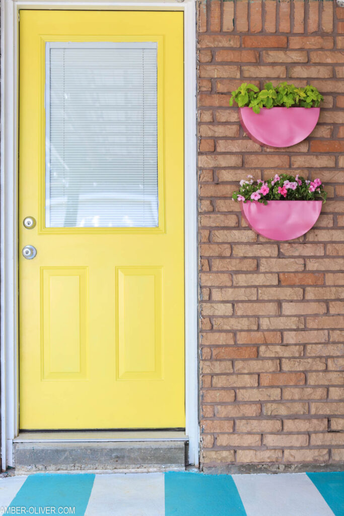 yellow backdoor with pink painted metal planters