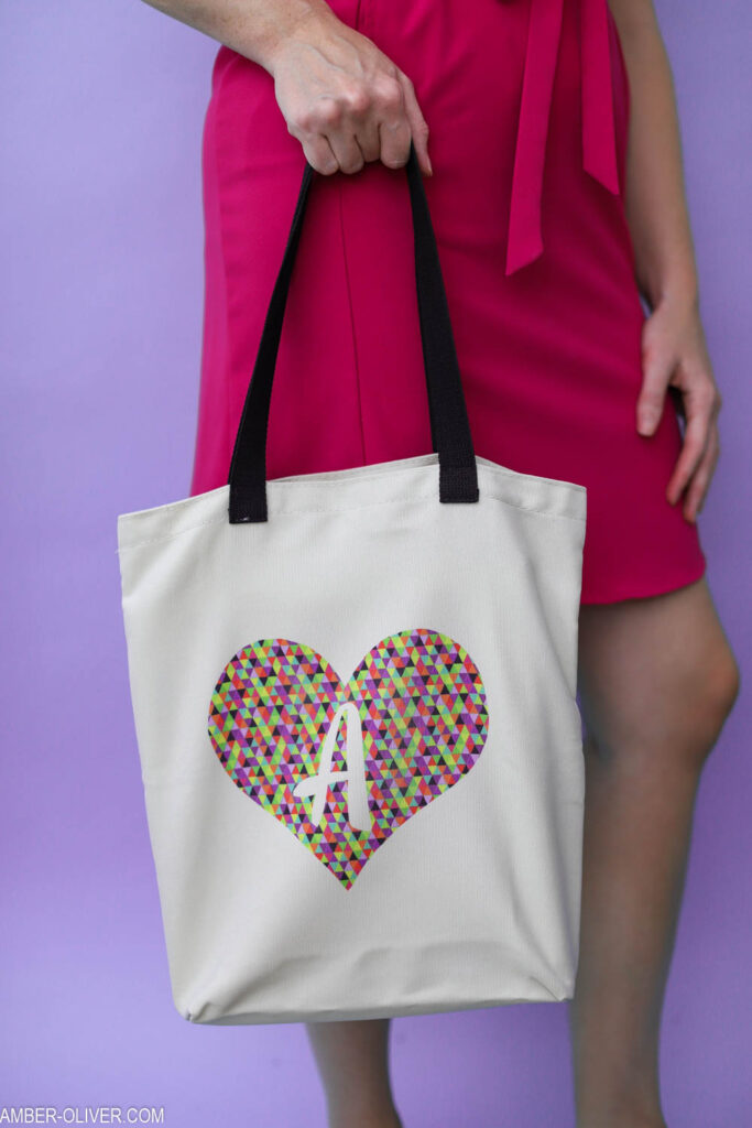 holding a tote bag made with cricut infusible ink