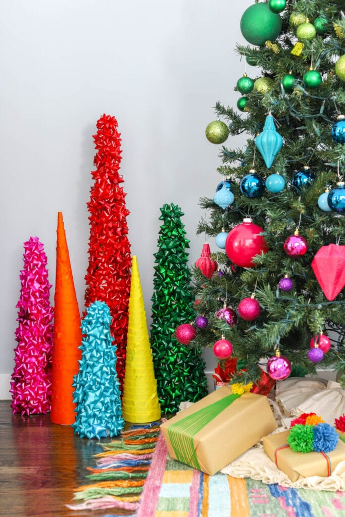 rainbow cone christmas trees in front on large tree