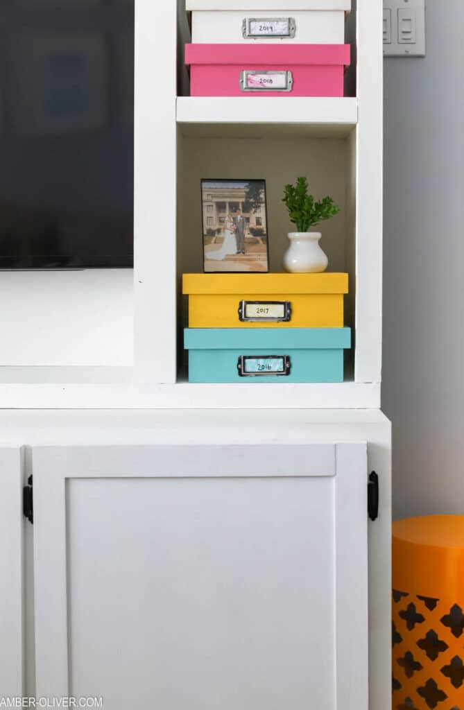 white diy entertainment center with memory boxes on the shelves