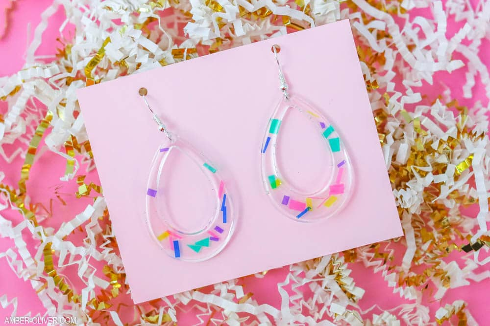 colorful DIY confetti earrings on a pink background