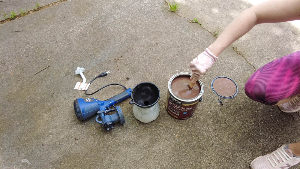 mixing up Behr semi transparent stain before using a paint sprayer to apply to a DIY wood fence